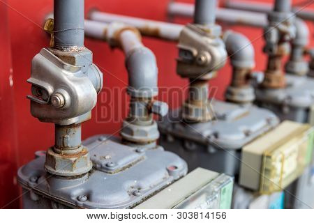 Abstract Building Power And Gas Meters With Pipes Going In A Red Wall