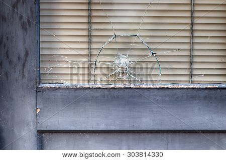Abstract Old Building Storefront Window With Bullet Hole In Daylight