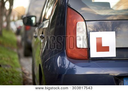 Learner Driver 'l' Sign At The Back Of A Blue Hatchback Compact Car
