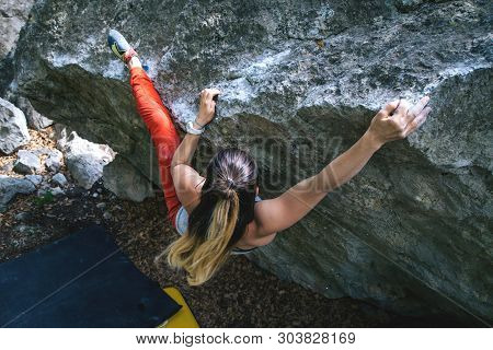 Beautiful Young Athletic Girl Climbing Hard Boulder Problem In Forest. Sport Climbing, Bouldering. O