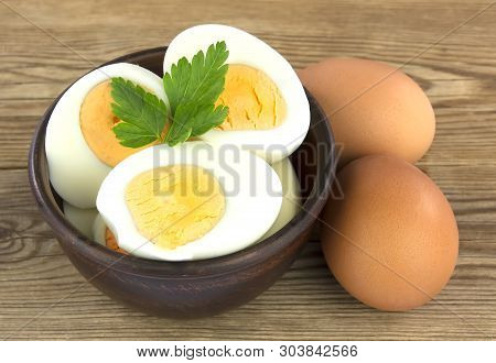 Sliced Boiled Eggs, With Parsley Leaves. Cooking A Salad With Boiled Eggs On Wooden Background.