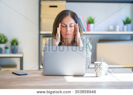 Middle age senior woman sitting at the table at home working using computer laptop with hand on head for pain in head because stress. Suffering migraine.