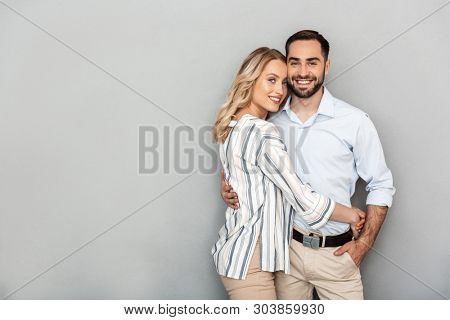 Photo of charming couple in casual clothing smiling and hugging isolated over gray background