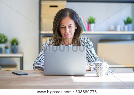 Middle age senior woman sitting at the table at home working using computer laptop Relaxed with serious expression on face. Simple and natural looking at the camera.