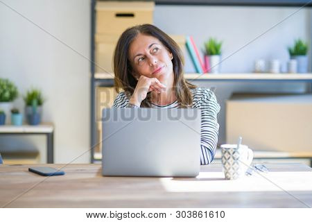 Middle age senior woman sitting at the table at home working using computer laptop with hand on chin thinking about question, pensive expression. Smiling with thoughtful face. Doubt concept.