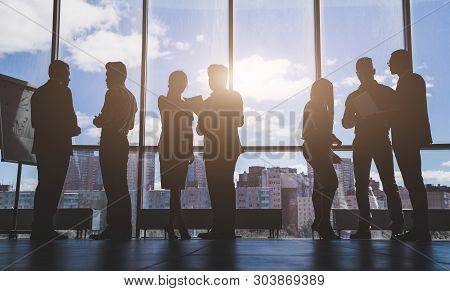 Silhouettes Of People Against The Window. A Team Of Young Businessmen Working And Communicating Toge