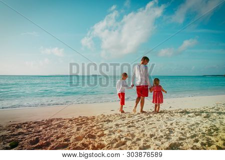 Father With Son And Daugther Walking On Beach