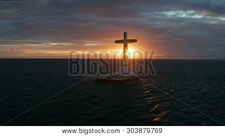 Catholic Cross In Sunken Cemetery In The Sea At Sunset, Aerial Drone. Colorful Sky During The Sunset