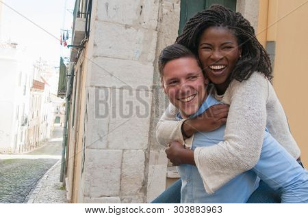 Guy carrying happy girlfriend on back in city. Happy interracial couple in street. Romance, tourism and happiness concept. Front view. poster