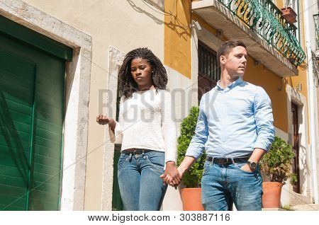 Bored disappointed African American girl holding hand of her Caucasian boyfriend. Interracial couple walking around old European city. Date or disappointed concept poster