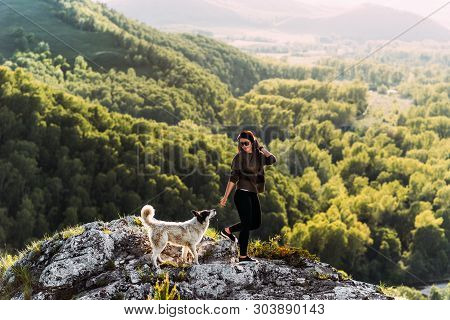 Woman With Dog Walking In The Mountains. Canine Friend. Walking With Your Pet. Travelling With A Dog