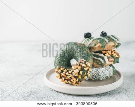 Vegan Doughnuts With Chia Seeds Topped With Healthy Spirulina Glaze With Pistachio, Desiccated Cocon