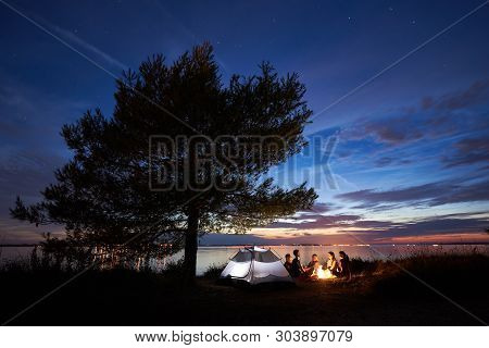 Group Of Five Young Tourists Sitting On Sea Shore Around Campfire Near Tent Under Big Tree And Blue