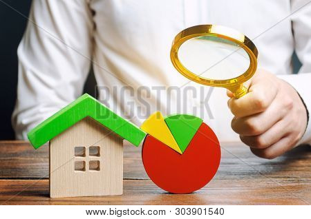 Businessman Holding A Magnifying Glass Over A Pie Chart And A Wooden House. Concept Analysis Of The