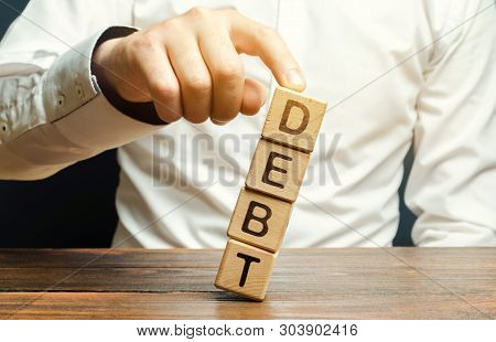 Businessman Removes Wooden Blocks With The Word Debt. Debt Relief Or Cancellation Is The Partial Or