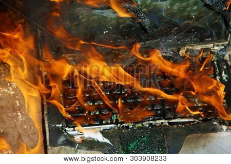 Computer Fire. A laptop computer engulfed in flames of hot fire. Smoke and Fire burn and melt a computer.  Computer damage or data destruction concepts.