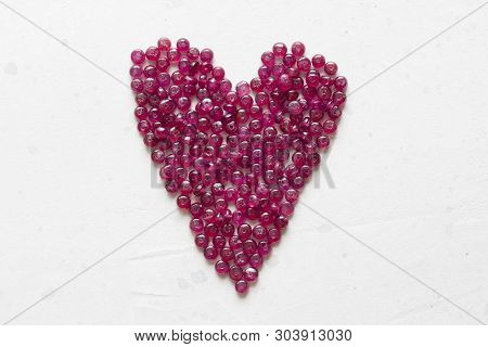 Ruby Stones Lie On A White Table In The Shape Of A Heart. Natural Stones Ruby, Ruby Beads. Pink Hear