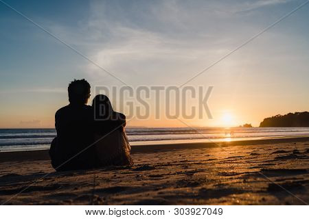Young Asian Couple Watching Sunset Near Beach, Sweet Couple Happy Relax Enjoy Love And Romantic Mome