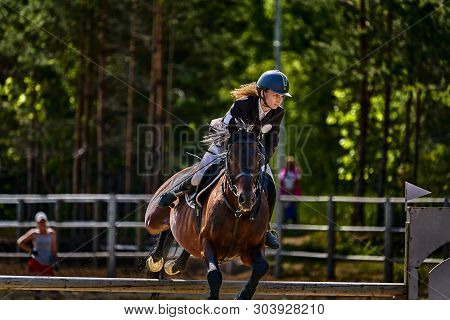 A Young Woman Jockey On A Horse Performs A Jump Across The Barrier. Competitions In Equestrian Sport