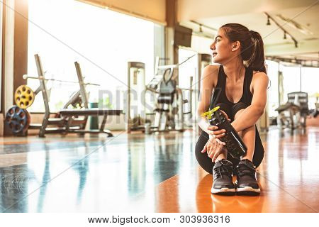 Sport Woman Relax Resting After Workout Or Exercise In Fitness Gym. Sitting And Drinking Protein Sha