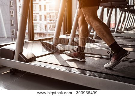 Close Up Of Sport Man Running On Treadmill In Fitness Gym At Condominium In Urban. People Lifestyles