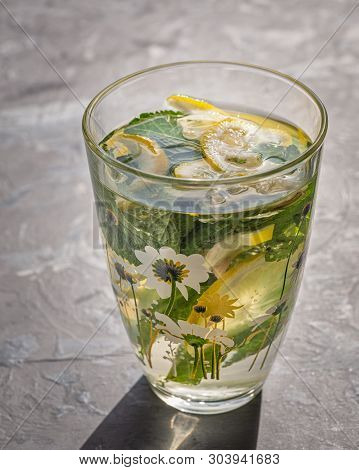 A cool drink that quenches your thirst on a hot day with melissa and lemons. Shot from close range. poster