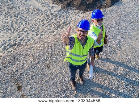 Aerial Image Of Two Engineers With Helmets And Vests, Holding Blueprints On Construction Site, Looki