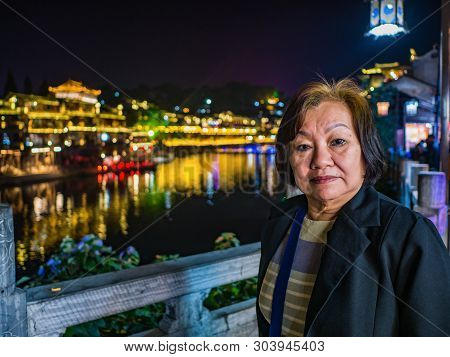 Portrait Photo Of Asian Senior Woman With Beautiful Nightscape Of Fenghuang Old Town.phoenix Ancient