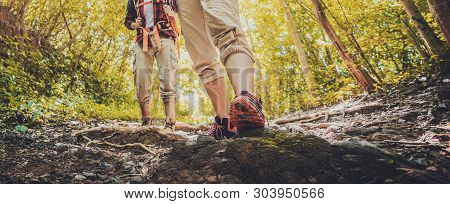 Lady Hiker Walking Through The Rocky Land. Focus On The Foot. Hiking Shoes In Action On A Mountain D