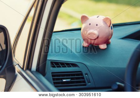 Pink Piggy Money Box Inside A Car Transportation. Saving Money For Vehicle Purchase. Successful Fina