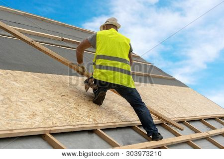 Concept Of Residential Building Under Construction. Professional And Qualified Roofer In Protective