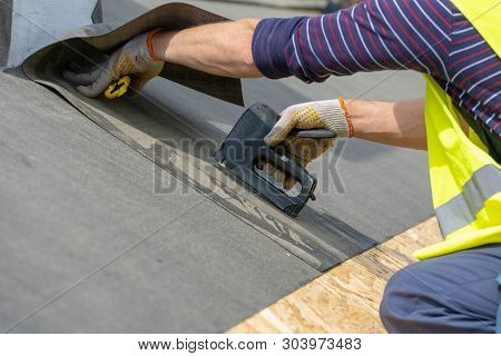 Close Up Photo Hands With Stapler Of Mature And Professional Working On Roof Top With Stapler, Attac