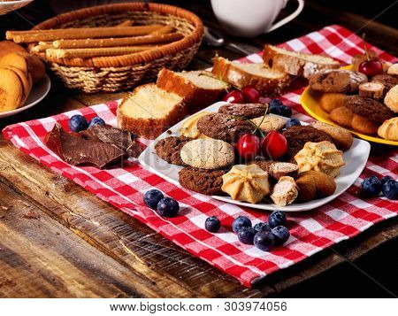 Oatmeal Cookies and sand chocolate cake with blueberries on wooden table with gingham cloth in farm style close up. Table setting breakfast for two with cups. Serve this dish hot.
