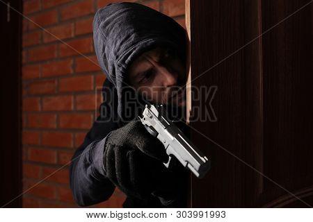 Man With Gun Spying Behind Open Door Indoors. Criminal Offence