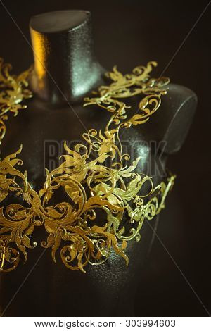 ABS filament, Haute couture, mannequin with piece of corset made with details of gold flourishes in Baroque or Renaissance style. Printed piece with 3d printer and ABS filament