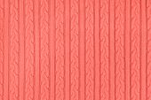 Trendy coral colored Knitwear Fabric Texture with Pigtails and stripes. Repeating Machine Knitting Texture of Sweater. Knitted Background. Color of the year 2019 poster