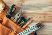 Carpentry tool belt on woodwork workshop desk with assorted tools of trade, top view with copy space poster