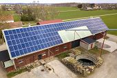 Top view of blue solar photo voltaic panels system on wooden building, barn or house roof. Renewable ecological green energy production concept. poster