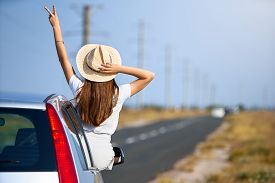 Slim Pretty Woman In Straw Hat Enjoying Road Trip On A Summer Day. Excited Young Female Raising Her