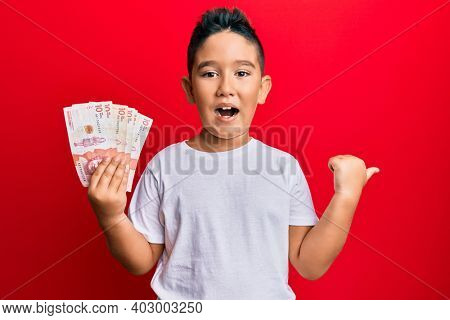 Little boy hispanic kid holding 10 colombian pesos banknotes pointing thumb up to the side smiling happy with open mouth