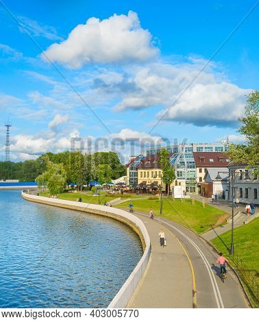 Minsk, Belarus - July 17, 2019: People Walking And Cycling By Svisloch River Embankment In Bright Su