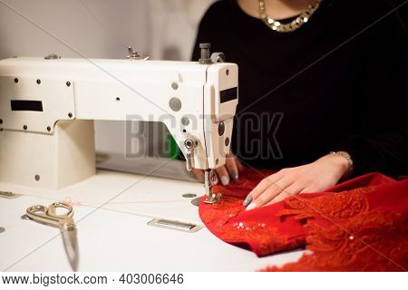 Dressmaker Working On The Sewing Machine. Tailor Making A Garment. Hobby Sewing As A Small Business