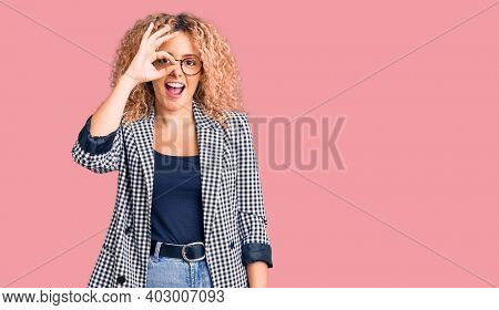 Young blonde woman with curly hair wearing business jacket and glasses doing ok gesture with hand smiling, eye looking through fingers with happy face.