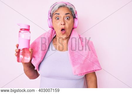 Senior hispanic woman wearing gym clothes and using headphones holding bottle of water scared and amazed with open mouth for surprise, disbelief face