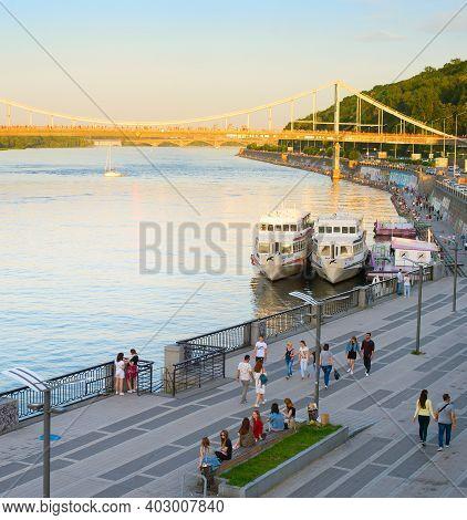 Kiev, Ukraine - June 08, 2020: People Walking By The River Dnipro Embankment At Sunet. Pedestrian Br