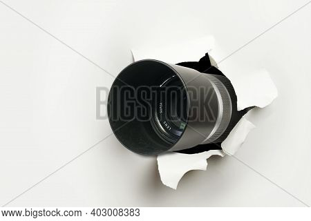 Concept Of Paparazzi Or Hidden Camera, Camera Lens Looks Out Through A Hole In White Paper Wall