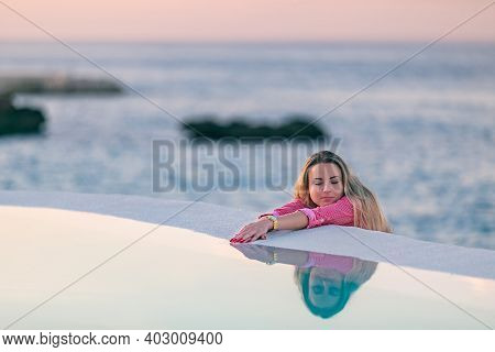 A Young Girl In A Red Shirt, At Dawn By The Sea Pool, Calm And Relaxed Looking At The Reflection In
