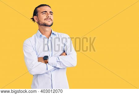 Young handsome man wearing business clothes looking to the side with arms crossed convinced and confident