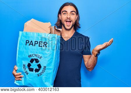 Young handsome man holding recycling wastebasket with paper and cardboard celebrating achievement with happy smile and winner expression with raised hand