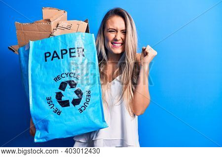 Young beautiful blonde woman recycling holding paper recycle bag full of paperboard screaming proud, celebrating victory and success very excited with raised arm